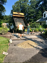 Picture of a truck and workers making asphalt repairs
