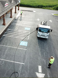 Picture of one of our workers sealcoating a parking lot